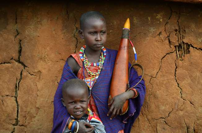Two young Masai boys with a gourd of milk, standing outside a traditional Masai dwelling made from sticks and plastered with cow dung.